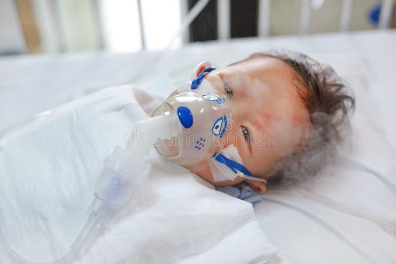 使用雾化器的小孩男孩治疗哮喘或肺炎疾病 患者的病态的男婴基于供并且有吸入疗法住宿  免版税库存图片