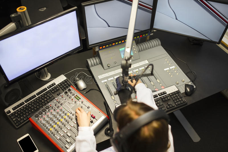 使用音乐搅拌器和屏幕的女性骑师在无线电演播室 免版税图库摄影