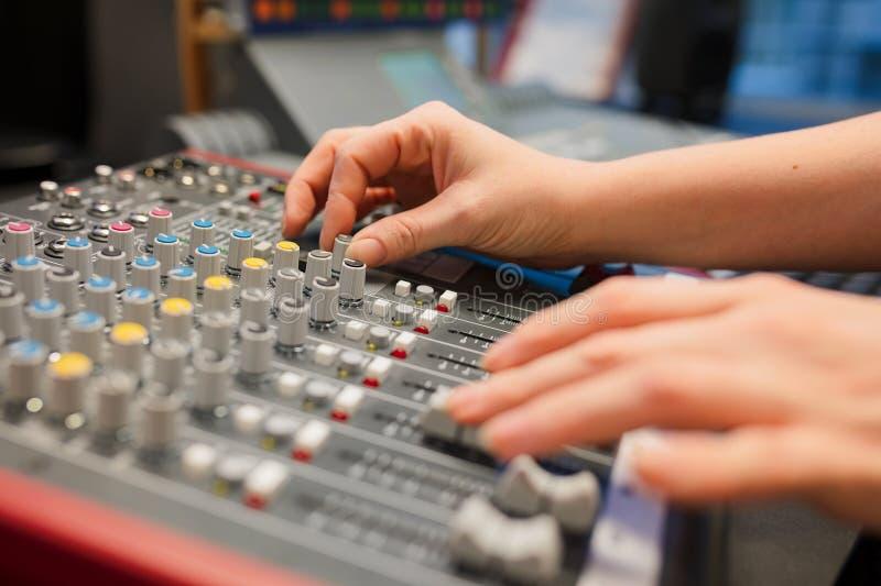 使用音乐搅拌器的女性无线电主人在演播室 库存图片