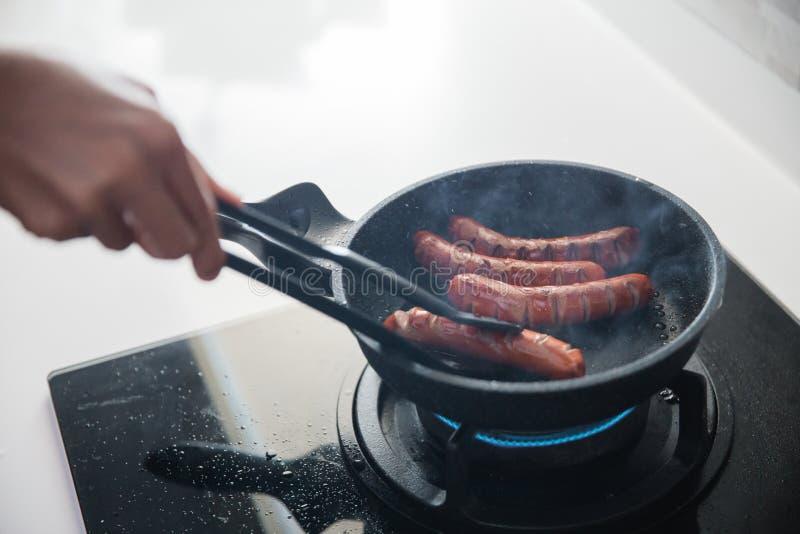 使用食物钳子的手对油煎香肠 免版税库存照片