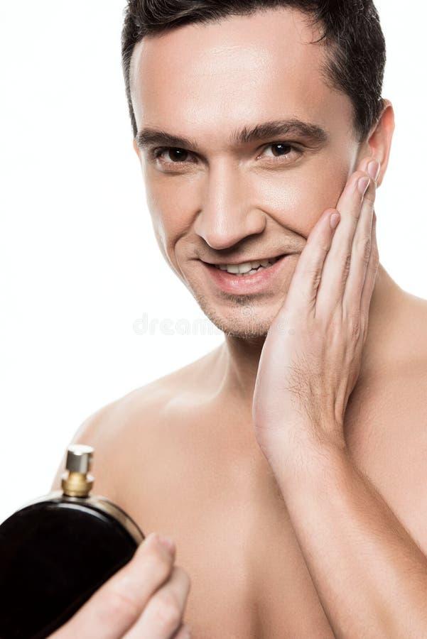 使用香水的英俊的人画象在早晨被隔绝的阵雨以后 免版税库存图片