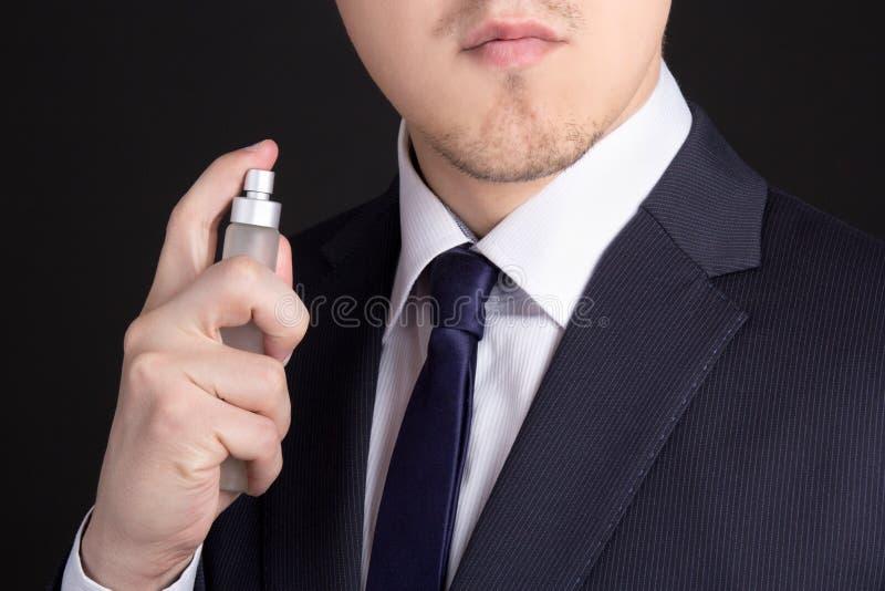 使用香水的英俊的年轻商人 库存照片
