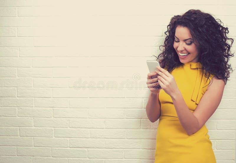使用高速互联网连接的妇女发短信在巧妙的电话 图库摄影