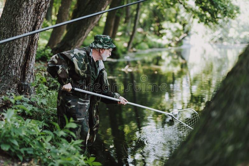 使用鱼网的专业年迈的钓鱼者在河 免版税库存照片