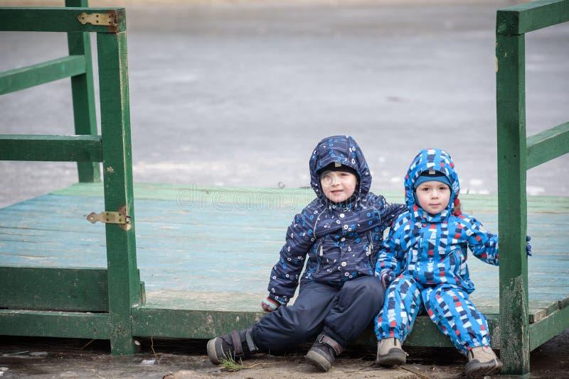 使用,在秋天风景,坐和微笑木码头在冻湖附近的两个弟弟 免版税库存照片