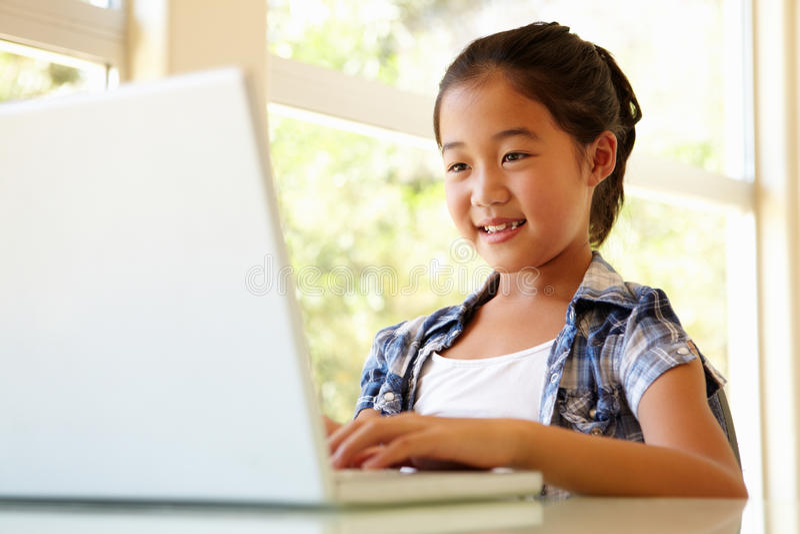 使用年轻人的女孩膝上型计算机 免版税库存照片