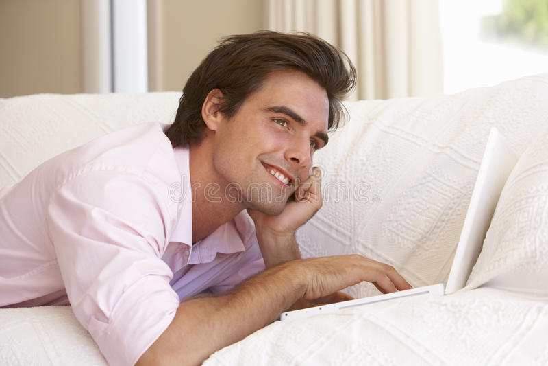 使用年轻人的家庭膝上型计算机人 库存照片