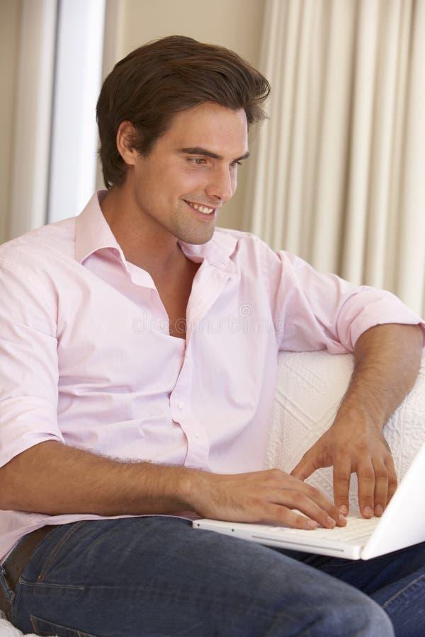 使用年轻人的家庭膝上型计算机人 免版税图库摄影
