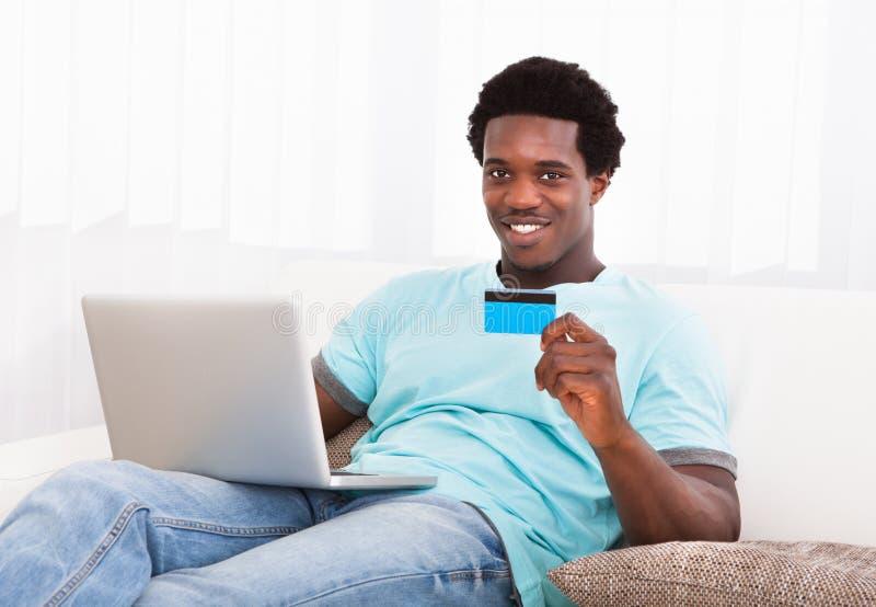 使用年轻人的愉快的膝上型计算机人 免版税库存图片