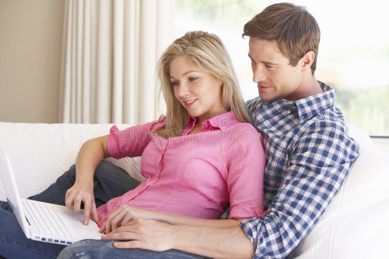 使用年轻人,夫妇回家膝上型计算机 库存图片