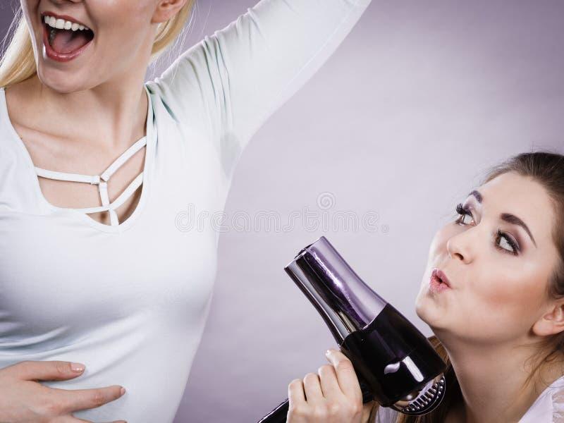 使用更加干燥的干燥的妇女她的朋友湿腋窝 免版税库存图片