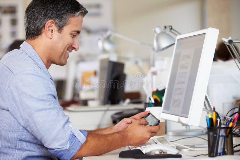 使用移动电话的人在服务台在繁忙的创造性的办公室 免版税库存图片