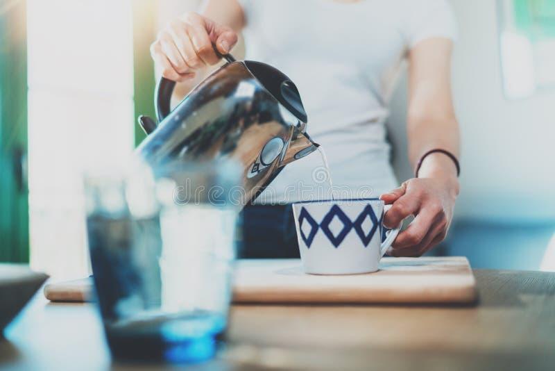使用水壶的少妇为在厨房做茶或无奶咖啡在室内部背景 妇女` s手倾吐水 免版税库存图片