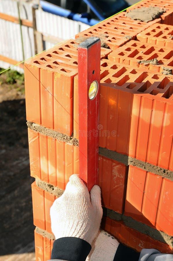 使用水平仪的瓦工检查新的砖墙 砌基本石工技术 免版税图库摄影