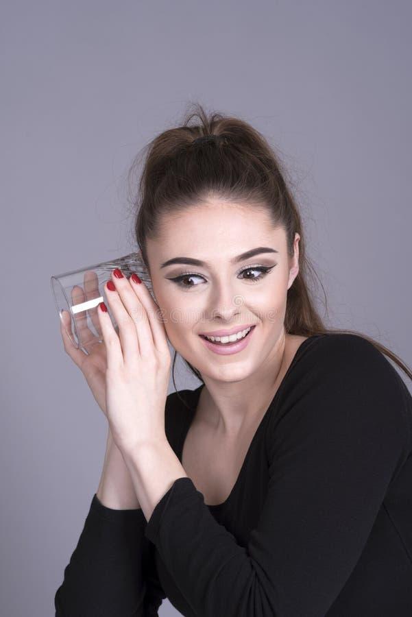使用水杯的少妇作为助听器 库存图片