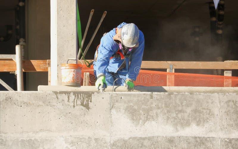 使用水泥沙磨机的建筑工人 免版税图库摄影