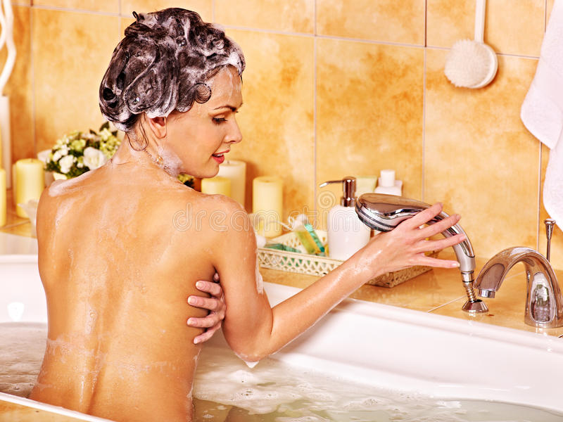 使用浴海绵的妇女在浴缸 免版税库存图片