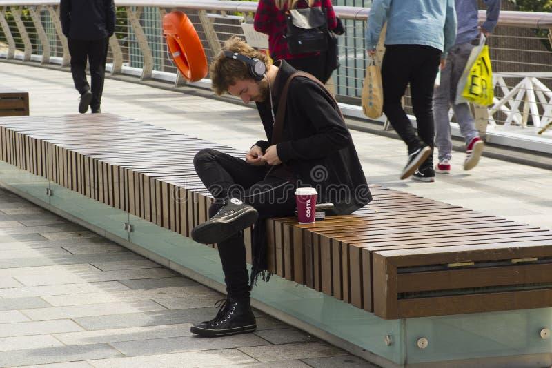 使用他的手机的一个年轻人,当放松在海滨在贝尔法斯特` s河Lagan时 免版税图库摄影