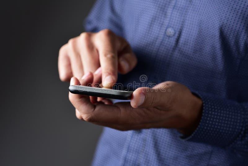 使用他的智能手机的年轻人户外 免版税库存照片