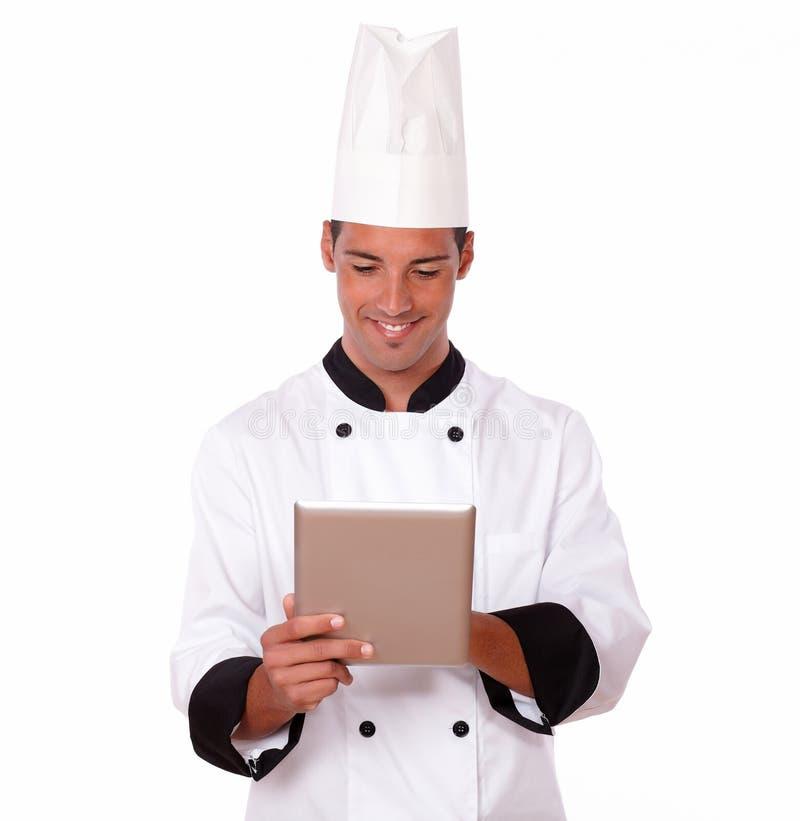使用他的片剂个人计算机的英俊的拉丁厨师 图库摄影