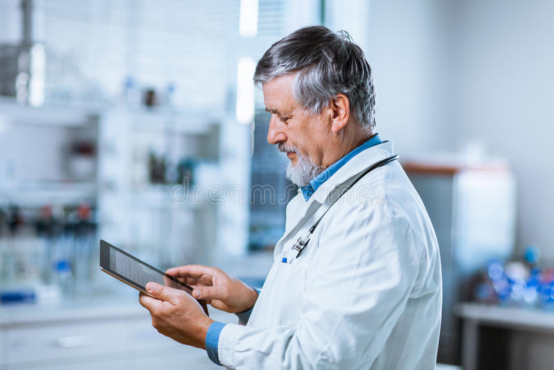 使用他的片剂计算机的资深医生在工作 库存照片