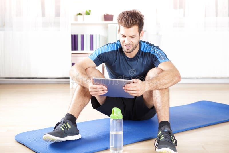 使用他的片剂计算机的适合的人在锻炼以后 库存图片