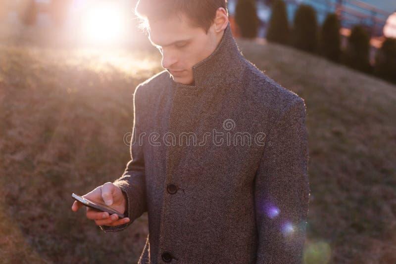 使用他的电话的一个英俊的年轻商人 免版税图库摄影