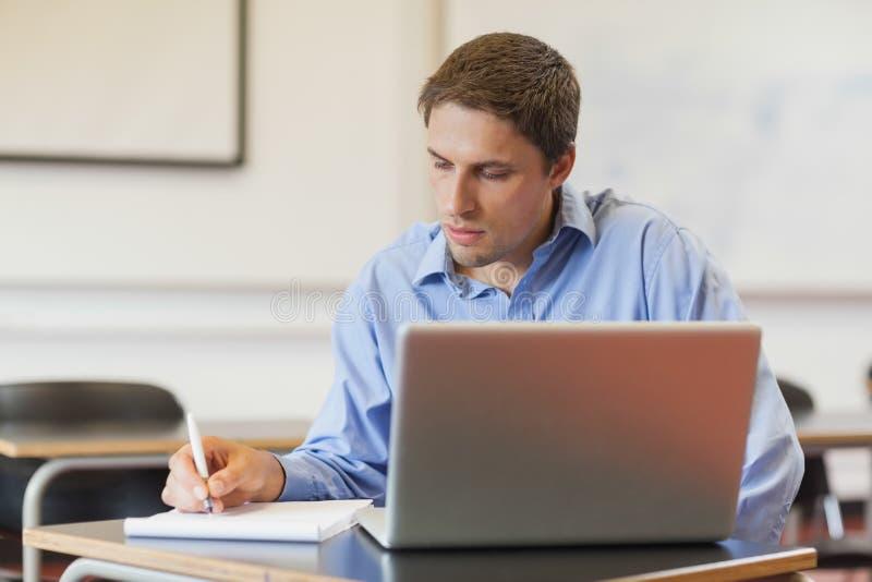 使用他的笔记本的被集中的男性成熟学生为学会 库存照片