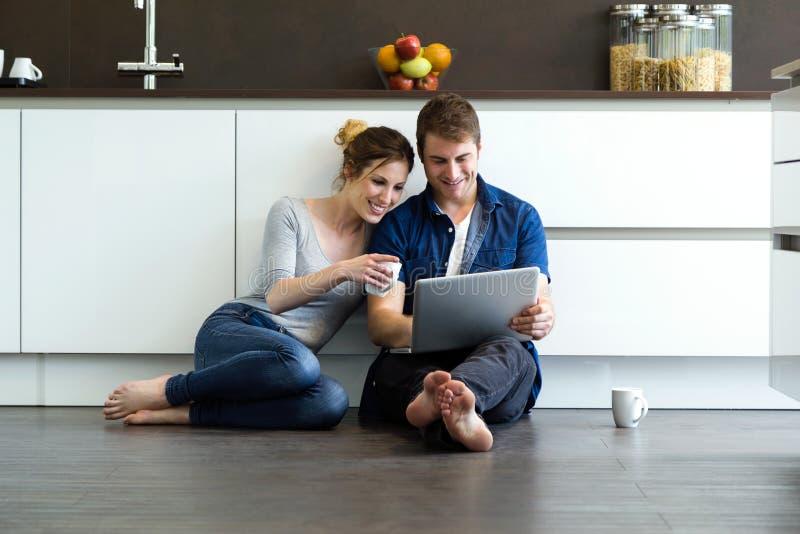 使用他们的美好的年轻夫妇数字式片剂在厨房里 免版税图库摄影