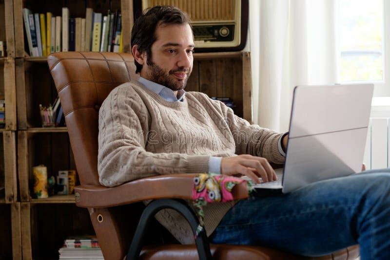 使用他的膝上型计算机和Wi-Fi互联网connecti,供以人员在家工作 库存图片