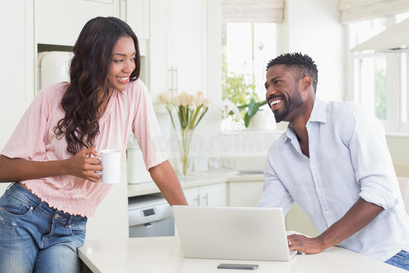 使用他们的膝上型计算机的愉快的夫妇在早餐 免版税库存照片