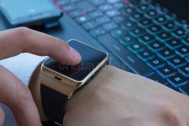 使用他的smartwatch app的商人在计算机个人计算机键盘和智能手机附近在每日光 免版税库存图片