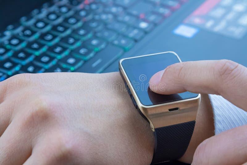 使用他的smartwatch app的商人在计算机在每日光的个人计算机键盘附近 免版税库存图片