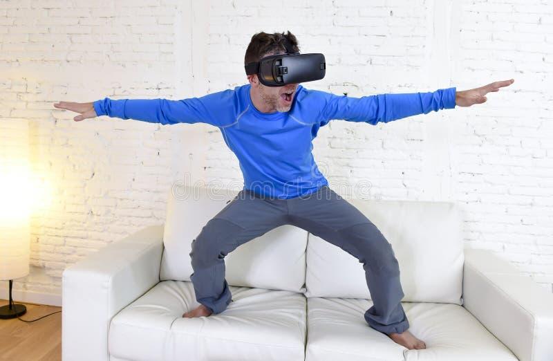 使用3d风镜虚拟现实冲浪被激发的愉快的人在家客厅沙发长沙发 免版税库存照片