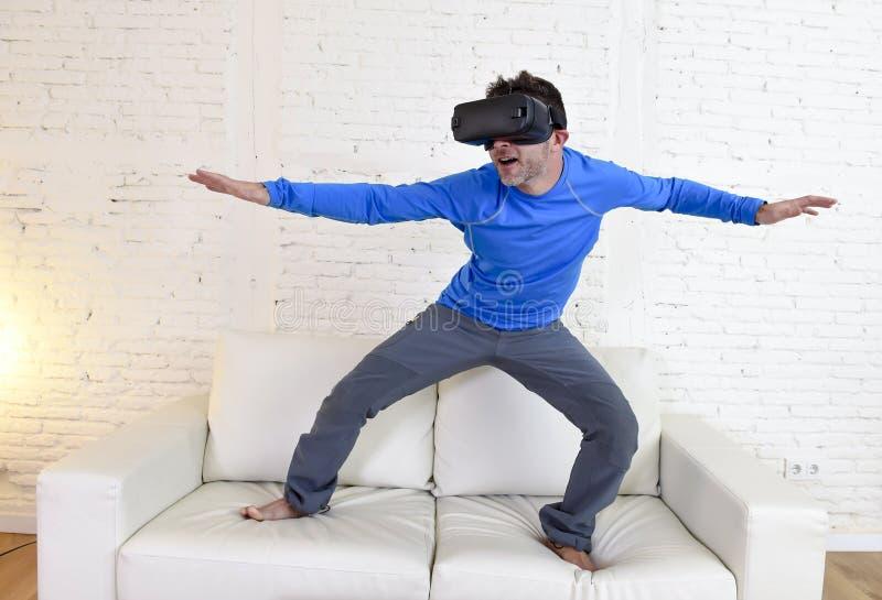 使用3d风镜虚拟现实冲浪被激发的愉快的人在家客厅沙发长沙发 库存照片