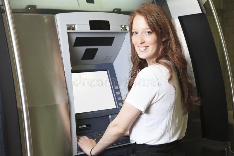 使用ATM机器的学生在学校 图库摄影