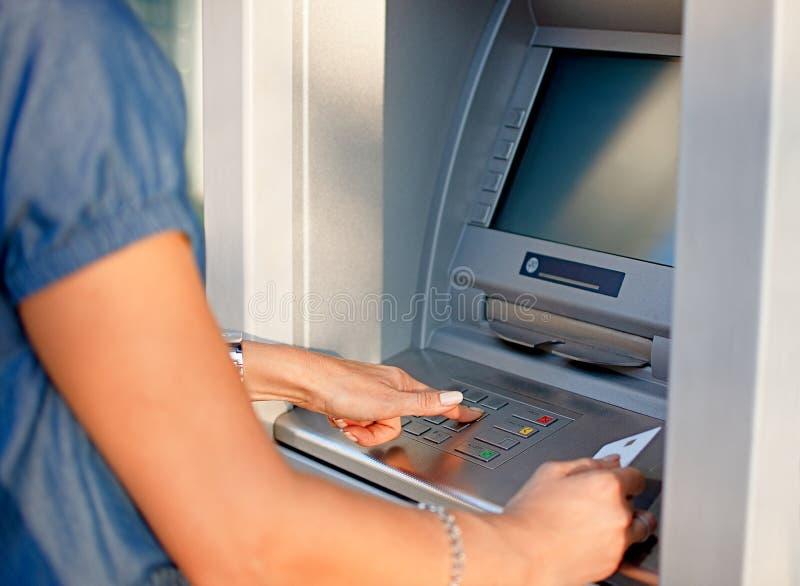 使用ATM的妇女拿着卡片和按在键盘自动出纳机的PIN安全数字 库存图片
