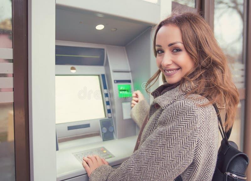 使用ATM的年轻愉快的妇女 图库摄影