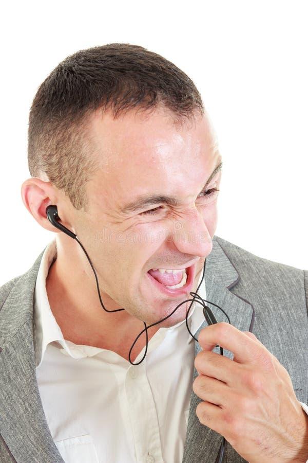 使用earbuds的年轻人呼喊在话筒 库存照片
