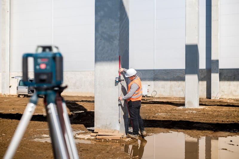 使用gps系统和经纬仪的专业测量员为在建造场所的正确水平 库存照片