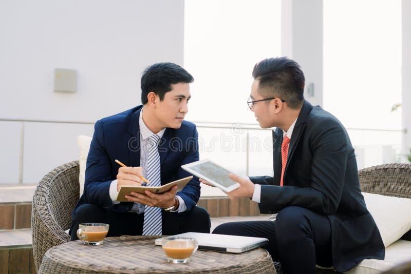 使用ipad的两位亚洲商业主管在城市公园 免版税库存图片