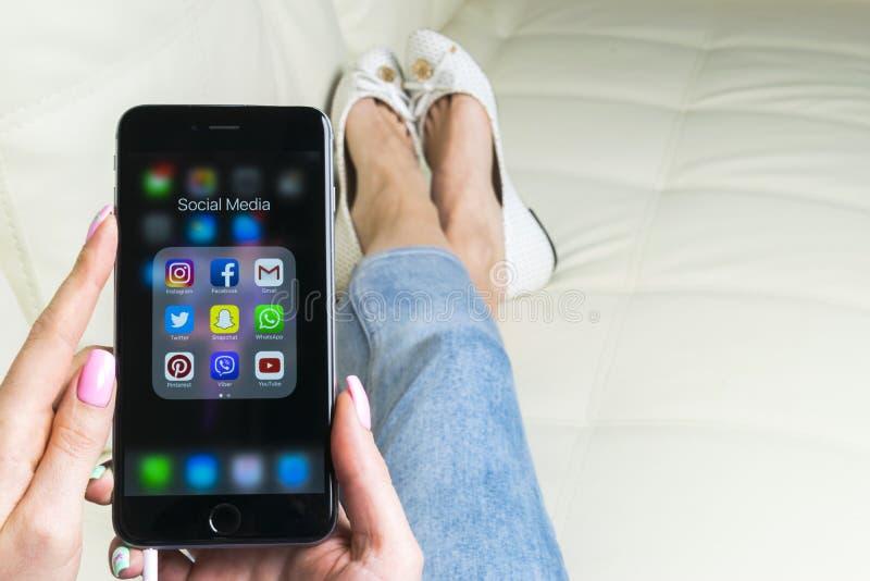 使用iphone 7的妇女手与社会媒介facebook, instagram,慌张,在屏幕上的谷歌应用象  智能手机 库存图片