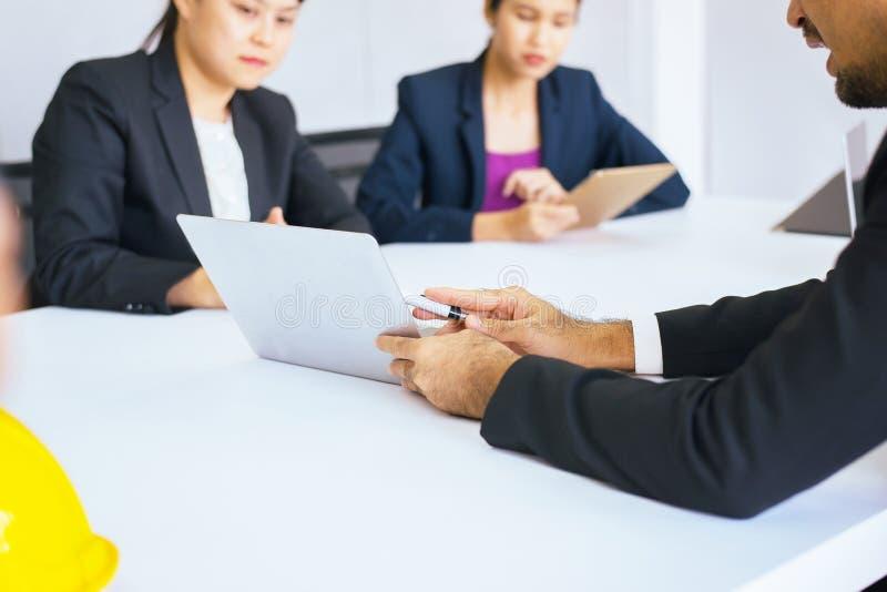 使用labtop的买卖人谈论在一起见面期间在会议室 免版税图库摄影