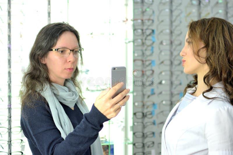 使用mobi,年轻俏丽的妇女在一家eyewear商店试穿眼睛玻璃在一个售货员和份额的帮助下在社会媒介 免版税图库摄影