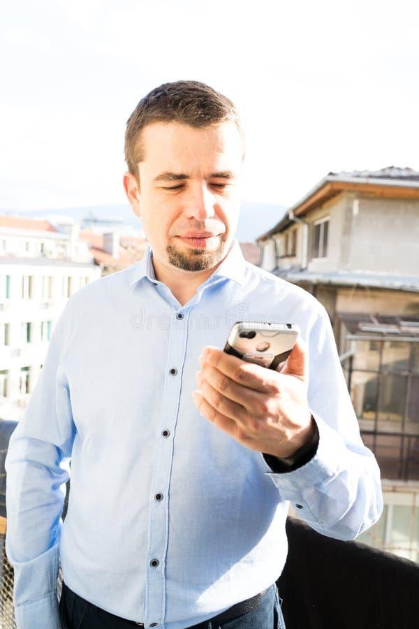 使用MOBIL电话的白种人人在阳台上 年轻画象蓝色的衬衣向下看屏幕 ?? 库存图片