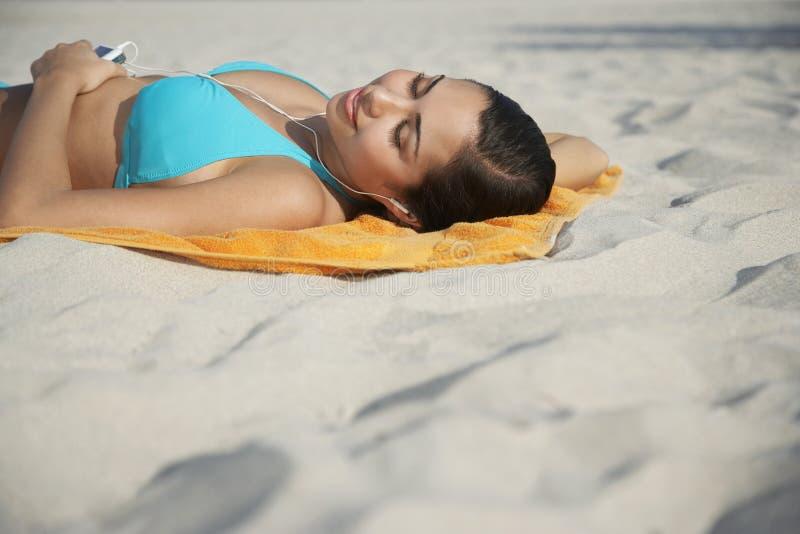 使用MP3播放器的十几岁的女孩说谎在海滩毛巾 库存照片