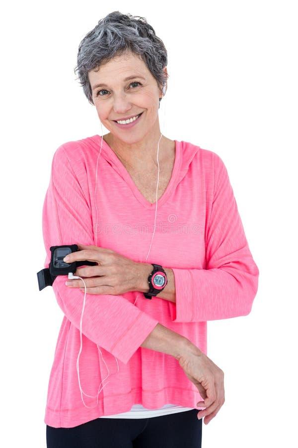 使用MP3播放器的愉快的妇女画象在臂章 库存图片