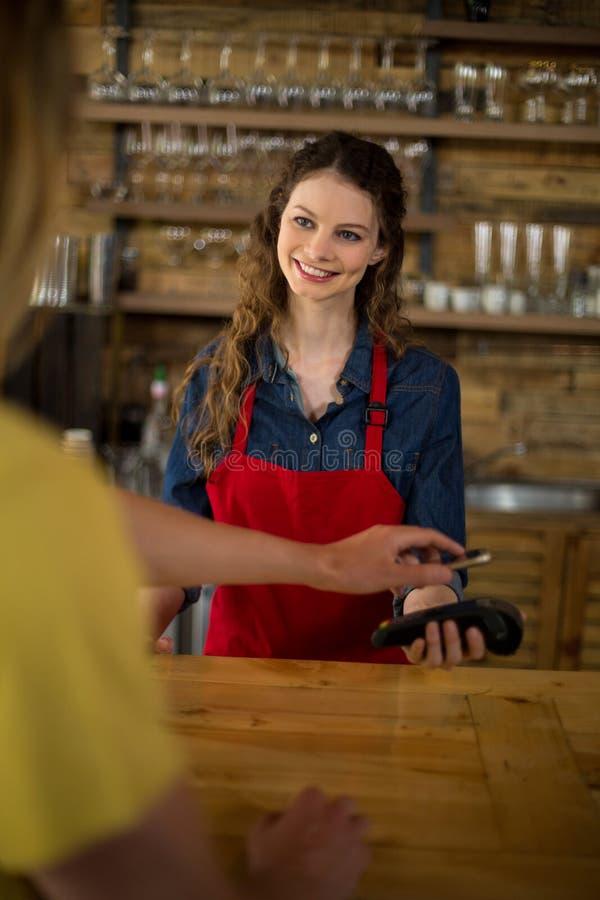 使用NFC技术,通过智能手机供以人员付帐 免版税图库摄影