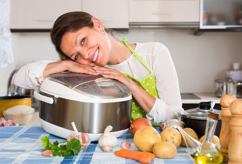 使用slo烹饪器材的愉快的妇女 免版税库存照片