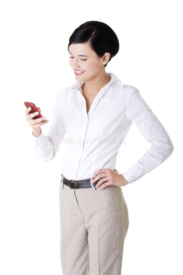 使用smartphone的聪明的新女实业家 免版税库存照片